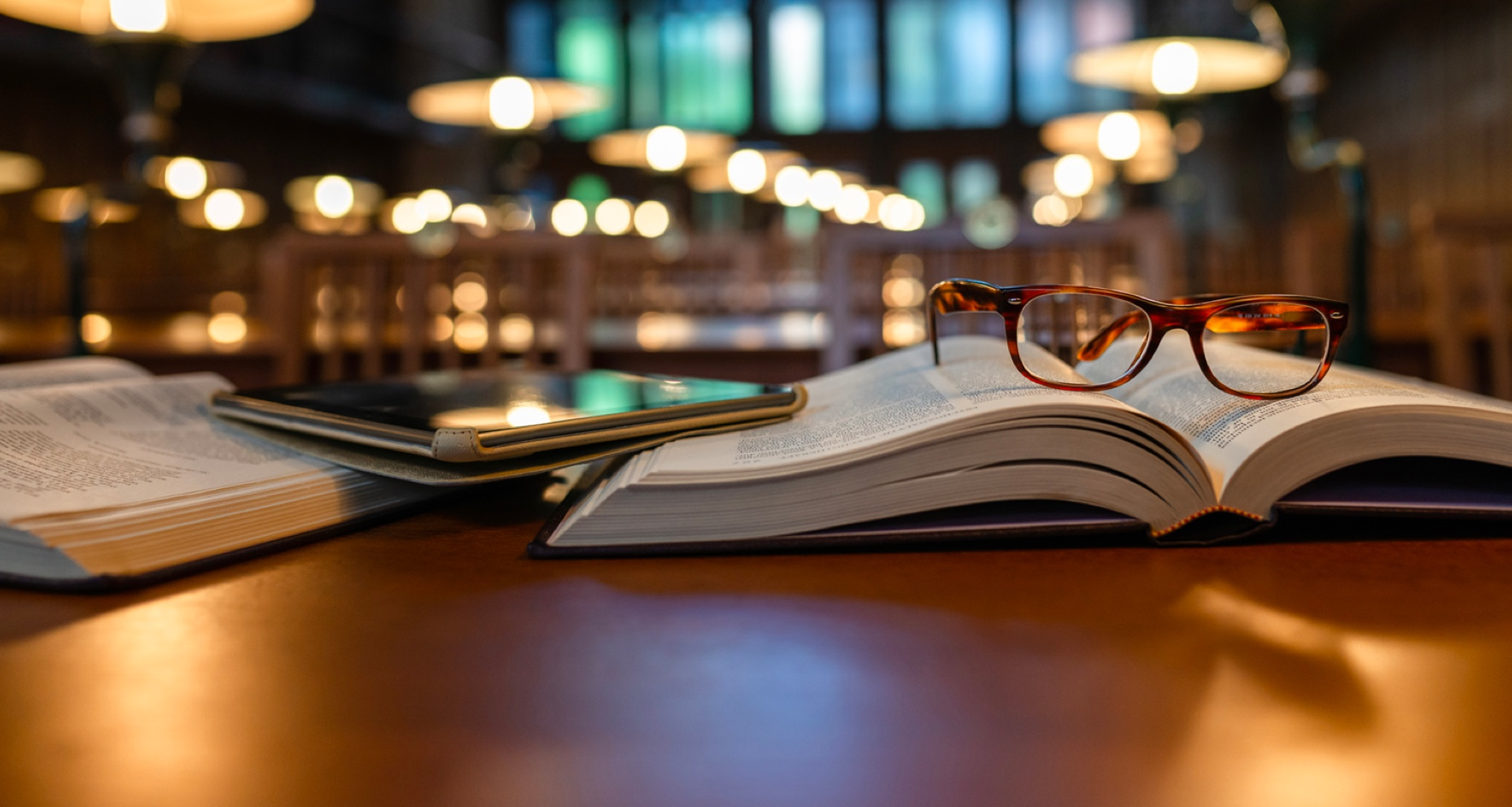 A pair of glasses on top of a book and e-tablet on a desk in a library.