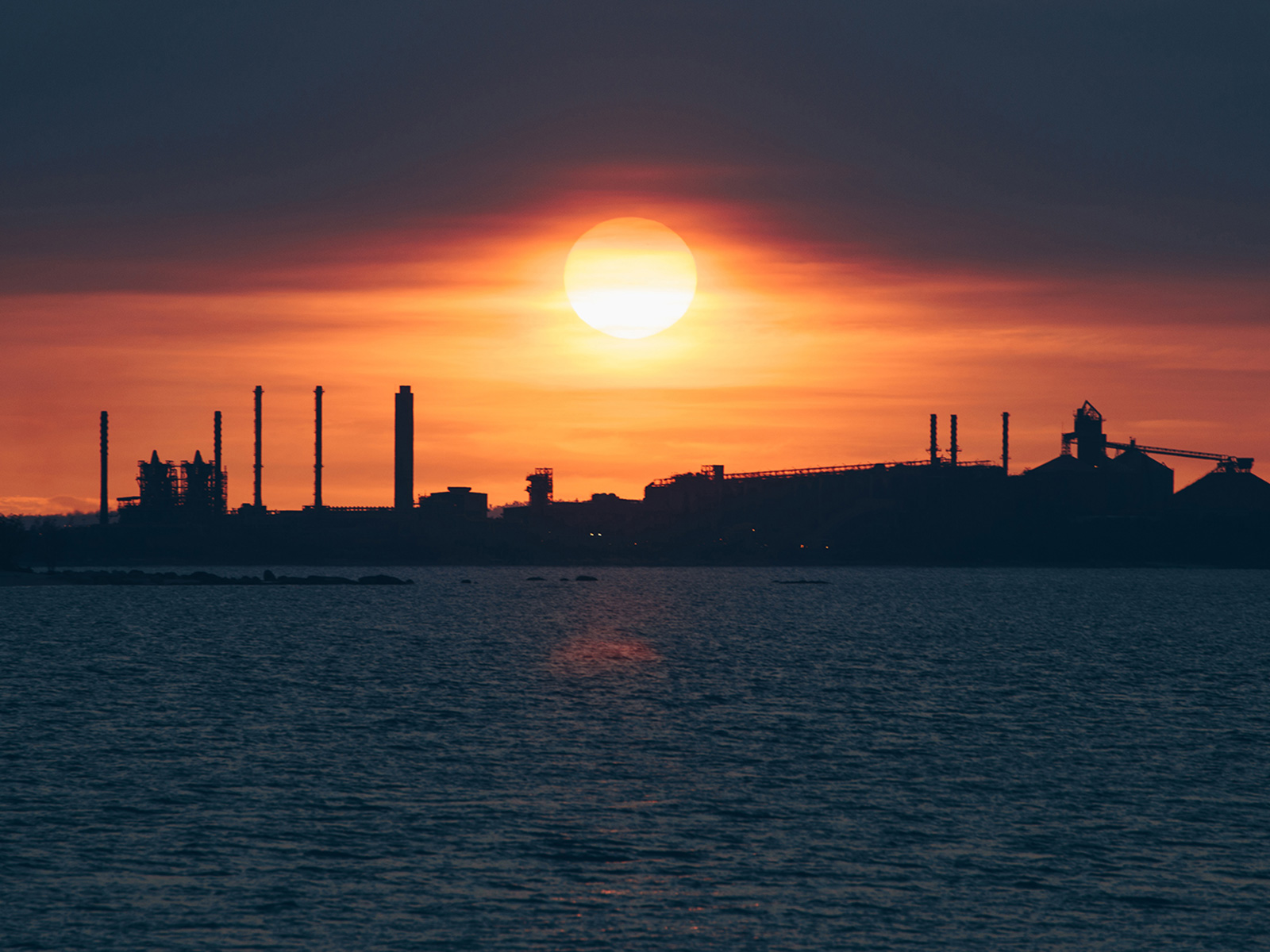 Sun setting over a power station