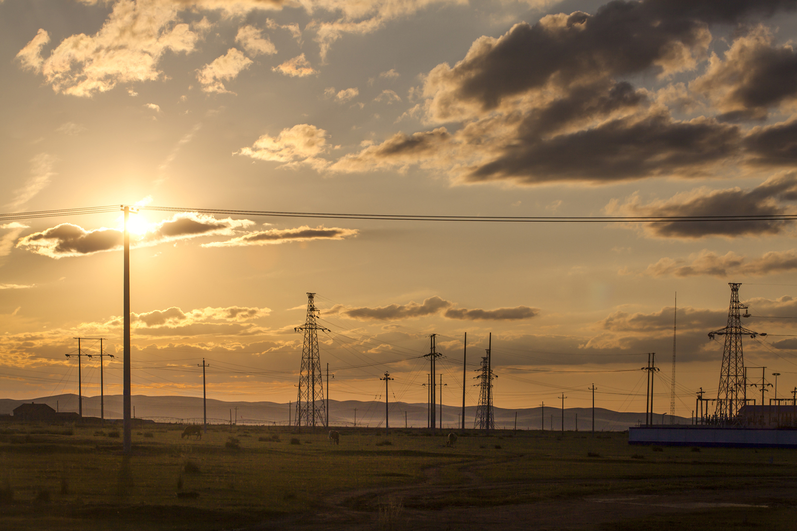 Transmission poles against sunset background