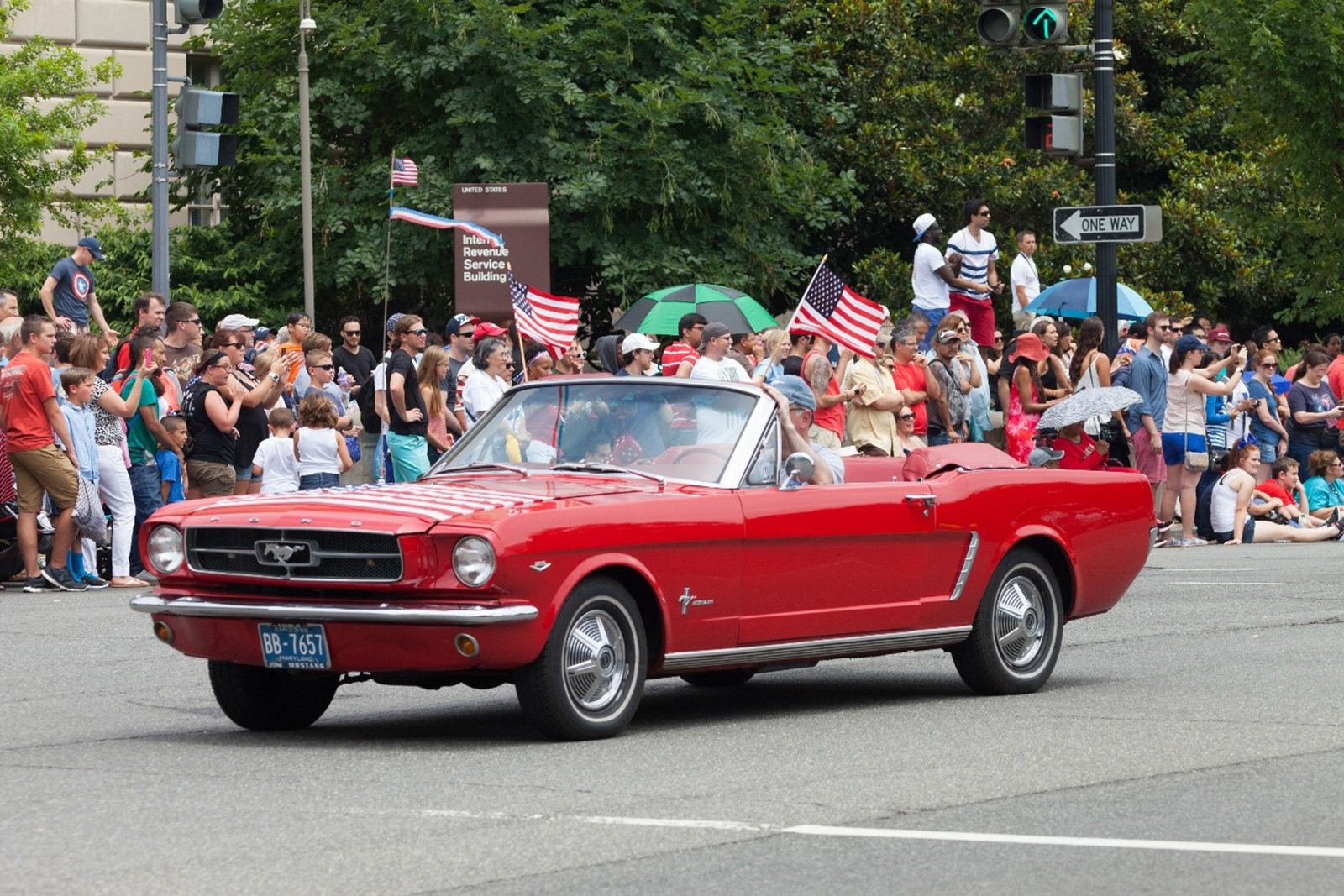 Red Ford driving on a road flanked with people and American flags