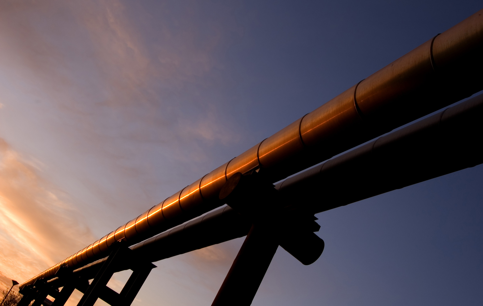 elevated gas pipes against sunset sky