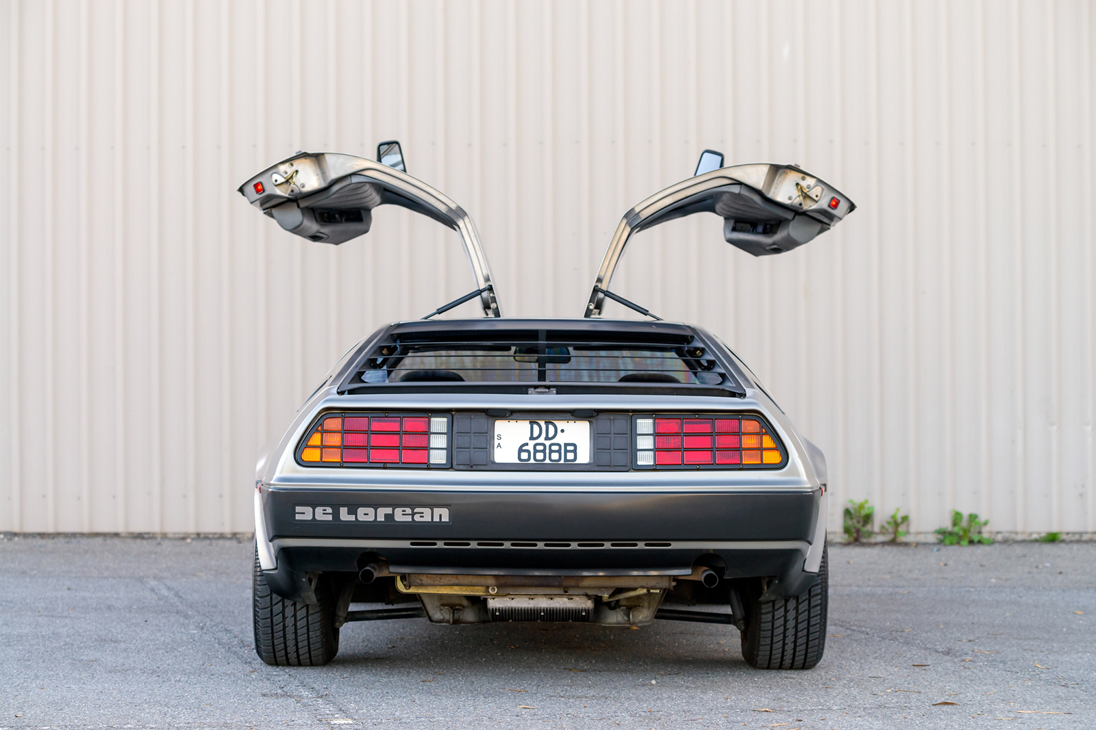 Rear of a Delorean car with its gull wing doors open