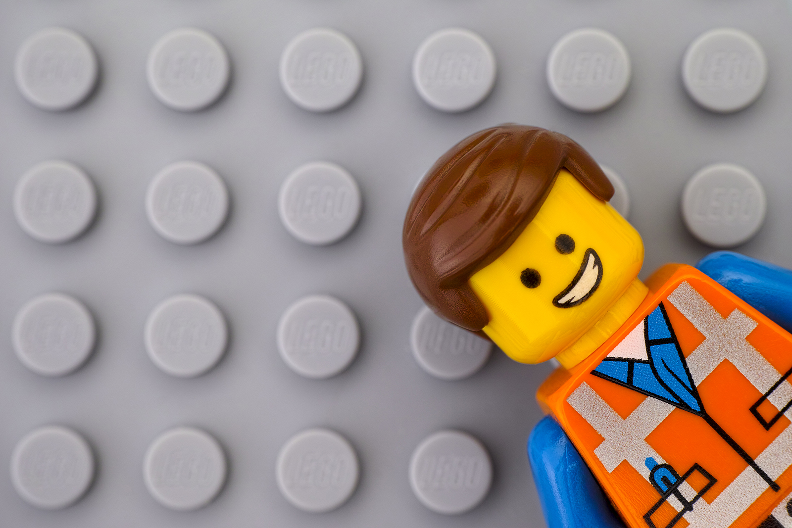 LEGO construction worker against grey brick background